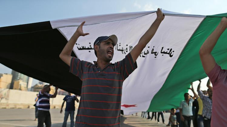 An anti-Syrian regime protester carries a large Syrian revolutionary flag during a demonstration in downtown of Beirut, Lebanon, Sunday, Oct. 14, 2012. Assir, a strong critic of Hezbollah leader Hasan Nasrallah and Syrian President Bashar Assad, has organized multiple protests over the past year in a bid to increase support for the Syrian uprising and mount an offensive against Nasrallah for openly supporting Assad's regime. (AP Photo/Hassan Ammar)