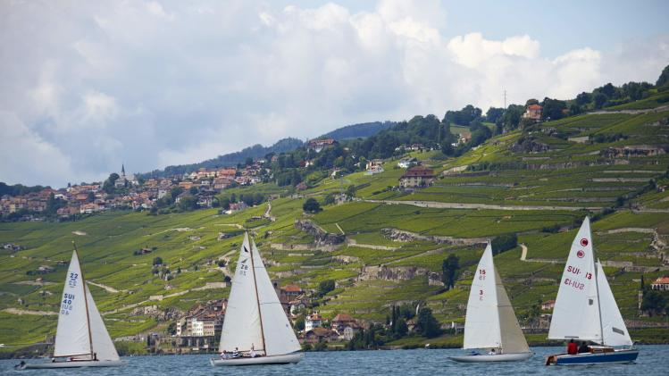 Wooden sailing boats take part in an exhibition regatta on Lake Leman near the Lavaux vineyards, near La Tour-de-Peilz