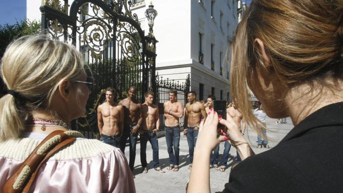 FILE - In this May 12, 2011 file photo, bystanders take snapshots as  bare-chested models pose in front of the Abercrombie & Fitch shop on the Champs Elysees in Paris, as  of the promotion of the  opening of the new U.S. brand shop in Paris. Abercrombie & Fitch Co. said Wednesday, May 18, that international sales helped pushed it to a first-quarter net income of $25 million. (AP Photo/Remy de la Mauviniere, file)