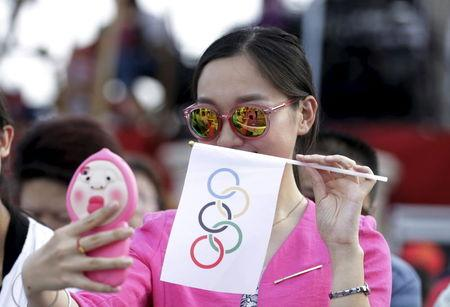 A local woman takes a selfie with an Olympics flag as she waits for IOC's announcement of the winner city for the 2022 winter Olympics bid in Chongli county of Zhangjiakou