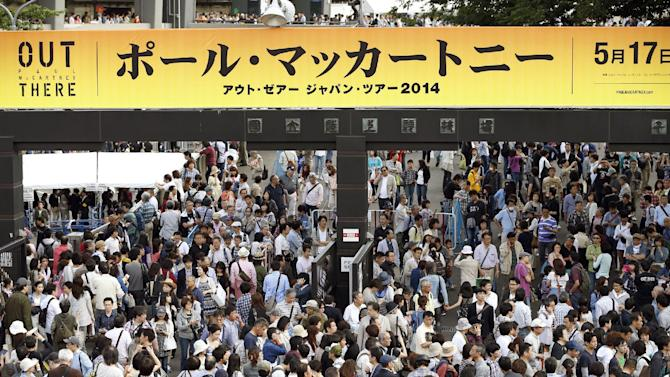 """Fans crowd at the gate of National Stadium following the cancellation of Paul McCartney's concert in Tokyo Saturday, May 17, 2014. McCartney canceled his show Saturday after he came down with a virus, but will make up for the lost performance Monday. The former Beatle said he plans to be well enough for Sunday's concert, although Saturday's """"Out There Japan Tour 2014"""" appearance at the stadium was called off. The banner written in Japanese reads: """"Paul McCartney."""" (AP Photo/Kyodo News) JAPAN OUT, CREDIT MANDATORY"""
