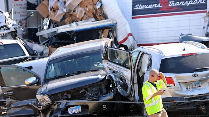 An emergency worker walks past a pile of cars from the accident on Interstate in Southeast Texas Thursday Nov. 22, 2012.  The Texas Department of Public Safety says at least 35 people have been injured in a more than 50-vehicle pileup.    (AP Photo/The Beaumont Enterprise, Guiseppe Barranco)  MANDATORY CREDIT,