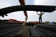 A Chinese worker unloads steel bars outside a factory in Huaibei, east China&#39;s Anhui province in August 2012. China&#39;s slowdown has hit commodity prices. BHP Billiton says record prices experienced over the past decade, driven by the demand shock, will not be there to support returns over the next 10 years