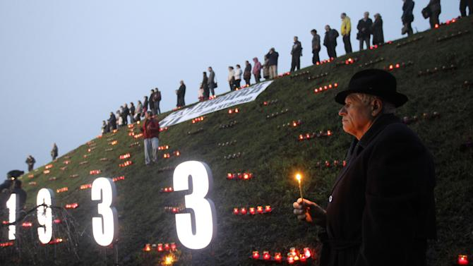 People light candles during a ceremony to commemorate victims of the 1932-33 Great Famine in Kiev, Ukraine, Saturday, Nov. 23, 2013. Ukraine marks the 80th anniversary of the terrible famine of 1932-33 in which millions of Soviet citizens perished.(AP Photo/Sergei Chuzavkov)