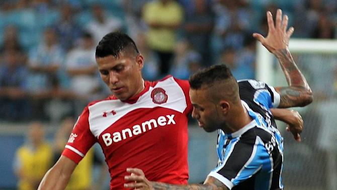 Moises Velasco of Mexico's Toluca, left, fights for the ball with Luan of Brazil's Gremio during a Copa Libertadores soccer match in Porto Alegre, Brazil, Tuesday, April 19, 2016. (AP Photo/Nabor Goulart)