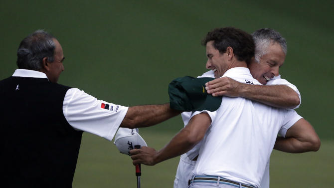 Angel Cabrera, of Argentina, congratulates Adam Scott, of Australia, while being hugged by caddie Steve Williams after his birdie putt on the second playoff hole to win the Masters golf tournament Sunday, April 14, 2013, in Augusta, Ga. (AP Photo/David Goldman)