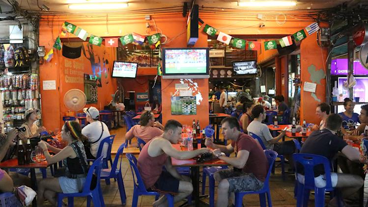 Tourists and locals eat and drink at a restaurant in Bangkok's Khaosan road, Thailand, Saturday June 14, 2014. The generals who seized power in Thailand have lifted a nationwide curfew, giving a green light for the capital's red-light districts, nightclubs and pubs to roar back to life. Late night revelry was planned in Bangkok to celebrate the return of Saturday night freedom for the first time in a month. (AP Photo/Apichart Weerawong)