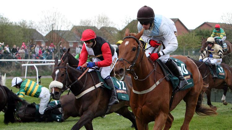 Synchronised, ridden by Tony McCoy, left, falls after jumping Becher's Brook the Grand National at Aintree Racecourse, Liverpool, England, Saturday April 14, 2012. Synchronised, who won the Cheltenham Gold Cup last month, suffered a fatal injury after falling early in the Aintree race, owner J.P. McManus announced. (AP Photo/Scott Heppell)