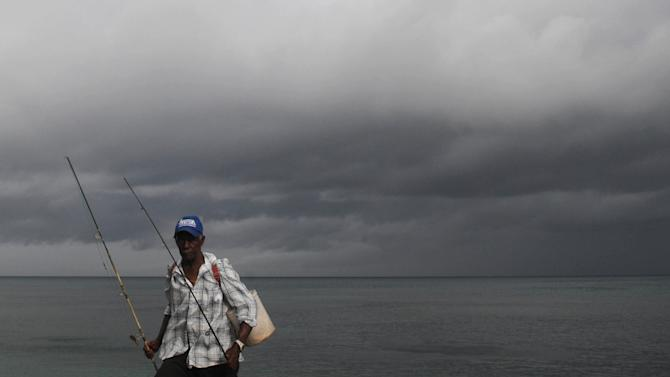 A fisherman walks home under cloudy skies along the shores of Santo Domingo, Dominican Republic, Thursday, Aug. 23, 2012. Tropical Storm Isaac churned toward the Dominican Republic and Haiti on Thursday, threatening to strengthen into a hurricane. (AP Photo/Manuel Diaz)