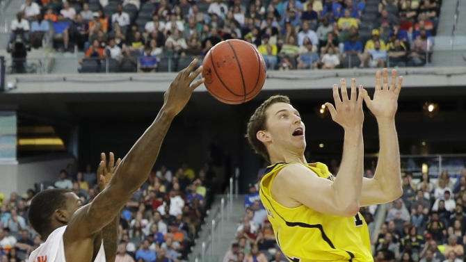 Michigan's Nik Stauskas (11) misses the pass as, Florida's Casey Prather defends during the second half of a regional final game in the NCAA college basketball tournament, Sunday, March 31, 2013, in Arlington, Texas. (AP Photo/David J. Phillip)