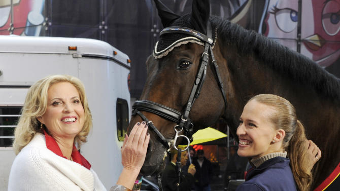 """This photo released by Good Morning America, Wednesday, Oct. 10, 2012, shows Ann Romney, wife of Republican presidential nominee Mitt Romney, left, standing with Lord Ludger and his rider Rebecca Hart on the set of the television show in New York. Romney said Wednesday that her love of horses helped her overcome her fear that multiple sclerosis would put her in a wheelchair. She was guest hosting ABC's """"Good Morning America"""" when she spoke about her depression after receiving the diagnosis 14 years ago. Hart recently won the USEF National Para-Equestrian Championship. (AP Photo/ABC, Ida Mae Astute)"""