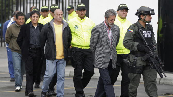 "Police officers escort alleged drug traffickers during their presentation to the press at a police station in Bogota, Colombia, Saturday, Sept. 3, 2011. About 36 suspected drug cartel members were detained during a joint operation with the US called ""Final Flight"". (AP Photo/Fernando Vergara)"