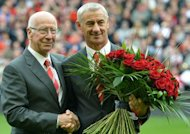 Manchester United's club ambassador Bobby Charlton (L) hands a bouquet of 96 roses to Liverpool's club ambassador Ian Rush (R) before the English Premier League football match between Liverpool and Manchester United at Anfield in Liverpool