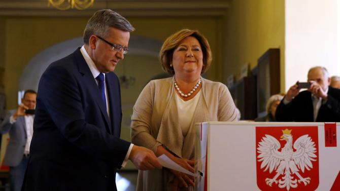 Poland's President and presidential candidate from the Civic Platform Party Komorowski casts his ballot next to his wife Anna at a polling station in Warsaw