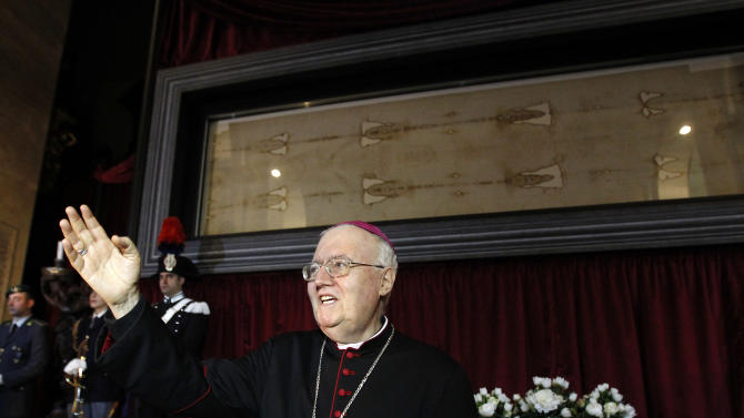 Archbishop Cesare Nosiglia presents the Holy Shroud, the 14 foot-long linen revered by some as the burial cloth of Jesus, on display during a preview for the press at the Cathedral of Turin, Italy, Saturday, April 18, 2015. The long linen with the faded image of a bearded man, that is the object of centuries-old fascination and wonderment, will be on display for the public from April 19 to June 24, 2015. Pope Francis said he is planning to visit the Holy Shroud during a a pilgrimage to Turin next June 21, 2015. (AP Photo/Antonio Calanni)
