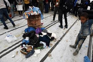 A boy stands near to  a pile of clothes left by migrants,…