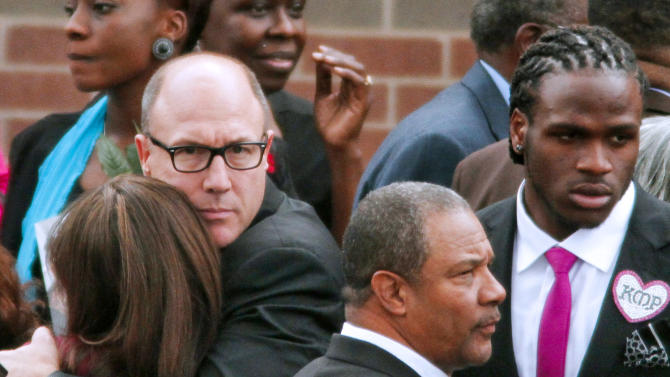 Kansas City Chiefs player Jamaal Charles, right, stands by as team general manager Scott Pioli, left, hugs Whitney Charles following the funeral service for Kasandra Perkins at the St. James Missionary Baptist Church on Saturday, Dec. 8, 2012, in Austin, Texas. Perkins was shot and killed last Saturday by her boyfriend, Kansas City Chiefs football player Jovan Belcher, before he proceeded to kill himself. Whitney Charles is Perkins' first cousin and wife of Jamaal Charles. (AP Photo/Jack Plunkett)