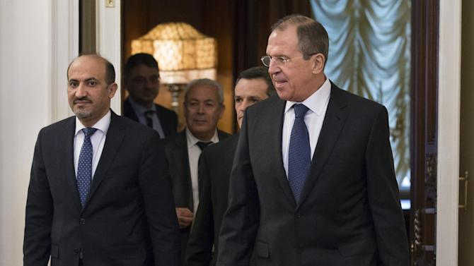 Russian foreign minister Sergey Lavrov, right, and Ahmad Jarba, left, who heads a delegation of the Syrian National Coalition enter a hall for their talks in Moscow on Tuesday, Feb. 4, 2014. Russia welcomed the National Coalition's participation in the Montreux conference on Syria as the confirmation of the coalition's choice in favour of a peaceful settlement of the Syrian conflict, Russian Foreign Minister Sergey Lavrov said today. (AP Photo/Alexander Zemlianichenko)