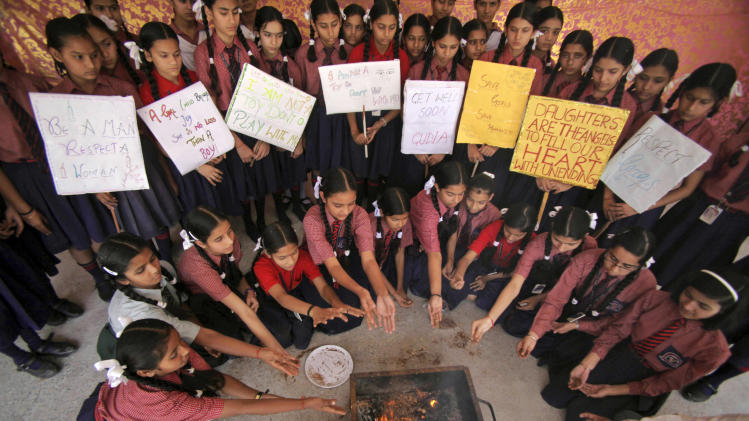 Indian schoolgirls perform rituals as they offer prayers for the speedy recovery of a 5-year-old girl who was raped and tortured in New Delhi, at Dewan Devi Public School in Jammu, India, Monday, April 22, 2013. A second suspect was arrested Monday in the rape of the girl who New Delhi police said was left for dead in a locked room, a case that has brought a new wave of protests against how Indian authorities handle sex crimes. (AP Photo/Channi Anand)