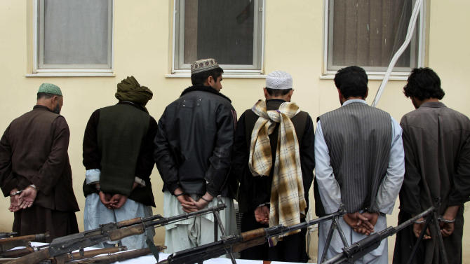 Former Taliban militants stand in line, hand-cuffed after turning in their weapons during a ceremony with the Afghan government in Herat, Afghanistan, Sunday, April 7, 2013. About six former Taliban militants from Herat province handed over their weapons as part of a peace-reconciliation program. (AP Photo/Hoshang Hashimi)