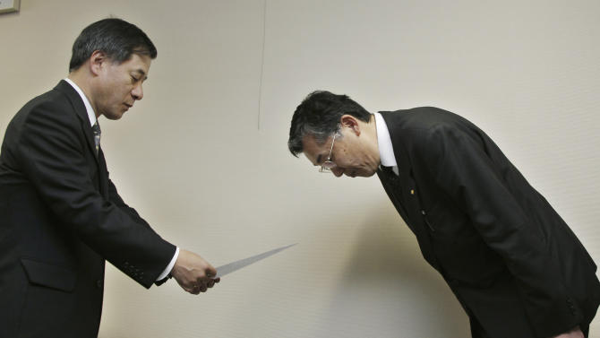 FILE - In this Feb. 9, 2010, file photo, Toyota Motor Corp. Managing Officer Hiroyuki Yokoyama, right, bows after submitting the company's formal recall notice for its 2010 Prius gas-electric hybrid and two other hybrid models to Ryuji Masuno, director general of the Road Transport Bureau of the Transport Ministry, at the ministry in Tokyo. Toyota recalled nearly 200,000 of its signature Prius green cars in Japan for braking problems. (AP Photo/Koji Sasahara, File)