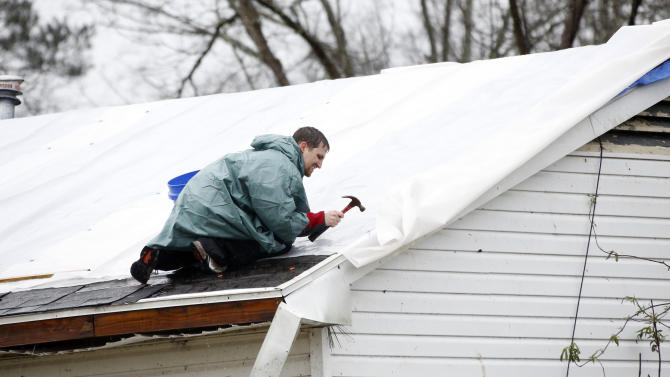 A residents makes quick temporary repairs to his roof Monday, Feb. 11, 2013, which was damaged from the Sunday's tornado in Hattiesburg, Miss. About 200 homes and mobile homes were damaged or destroyed. Rain fell today as people tried to put tarps over leaky roofs and move belongings to dry ground. (AP Photo/Rogelio V. Solis)