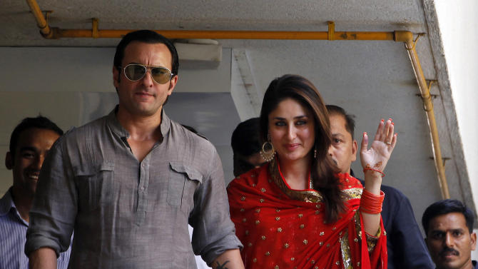 Bollywood stars Saif Ali Khan, left, and Kareena Kapoor step out on a balcony to greet waiting fans after getting married in Mumbai, India, Tuesday, Oct. 16, 2012. The Press Trust of India reported the couple married Tuesday in a small official ceremony in Khan's house in Mumbai with a few friends and family members in attendance.  (AP Photo/ Rajanish Kakade)