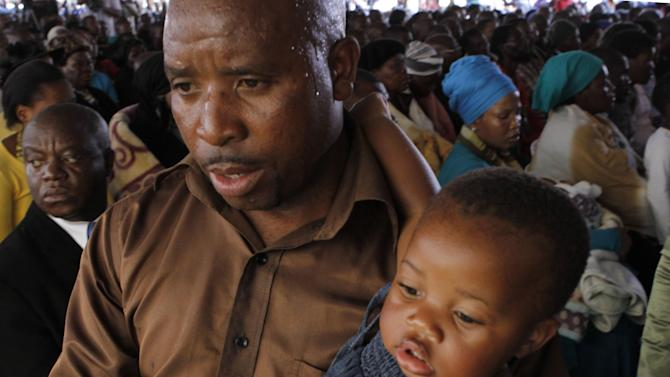 Mourners attend a memorial service at the Lonmin Platinum Mine near Rustenburg, South Africa, Thursday, Aug. 23, 2012 for striking miners that were shot and killed by police last week.   (AP Photo/Denis Farrell)