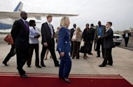 "US Secretary of State Hillary Clinton(C) and South Sudan's Foreign Minister Nhial Deng Nhial, far left, walk to a vehicle as the Secretary arrives for her first visit to South Sudan at Juba International Airport. Clinton warned that ""significant challenges"" face the world's youngest nation, with ""persistent poverty in a land rich with natural resources."""