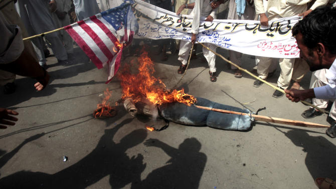 Pakistani protesters burn a representation of a U.S. flag and an effigy of President Barack Obama during a rally in Peshawar, Pakistan as a part of widespread anger across the Muslim world about a film ridiculing Islam's Prophet Muhammad, on Thursday, Sept. 20, 2012. Hundreds of Pakistanis angry at an anti-Islam film that denigrates the religion's prophet clashed with police in the Pakistani capital Thursday, the most violent show of anger in a day that saw smaller demonstrations in Indonesia, Iran and Afghanistan. (AP Photo/Mohammad Sajjad)