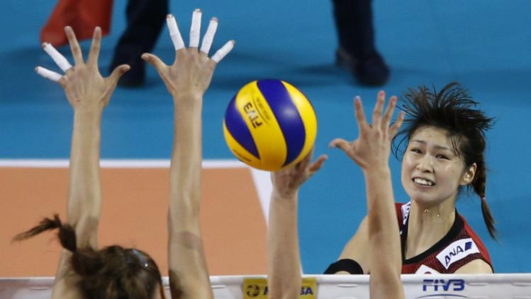 Kimura of Japan spikes the ball against Russia's Kosianenko and Zaryazhko during their FIVB Women's Volleyball World Grand Prix 2014 final round in Tokyo