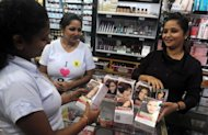 An Indian employee of a cosmetic shop displaying L'Oreal products in Siliguri on September 15. Global cosmetic firms are turning to emerging markets in the hunt for sales, but they face a challenge tailoring their beauty products to suit new customers in India, China and elsewhere