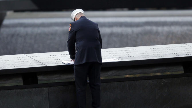 A firefighter makes a rubbing of a victim's name as friends and relatives of the victims of the Sept. 11 terrorist attacks on the World Trade Center gather for a ceremony marking the 11th anniversary of the attacks at the National September 11 Memorial in New York, Tuesday, Sept. 11, 2012. (AP Photo/Jason DeCrow)