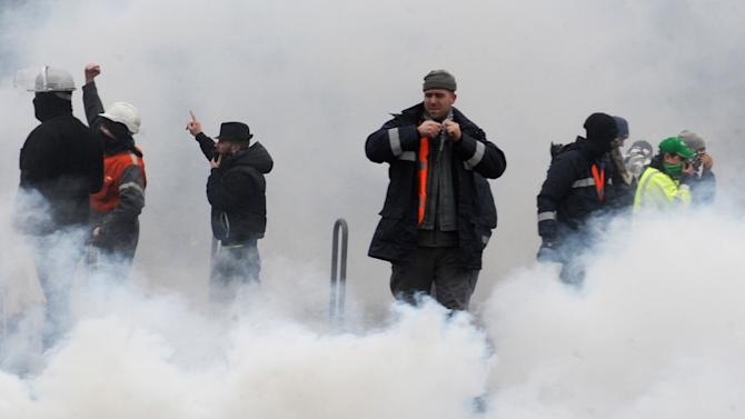 Steel workers from ArcelorMittal demonstrate amidst tear gas from police, Wednesday Feb. 6, 2013, near the European Parliament in Strasbourg, eastern France. Steel workers coming from Belgium, Luxemburg and northern France gathered to protest against jobs cuts as ArcelorMittal was presenting its fourth quarter earnings. Charges related to its ailing European business and a drop in the value of its assets saw ArcelorMittal SA, the world's largest steel maker, post a near US dlrs 4 billion (euro 3 billion) loss for the fourth quarter. (AP Photo/Christian Lutz)