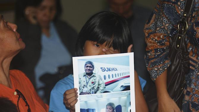 Tasya Kamagi, 10, holds the pictures of his father Steven that were taken when he boarded a Russian-made Sukhoi Superjet-100 that crashed on a mountainous area in West Java, at Halim Perdanakusuma Airport in Jakarta, Indonesia, Thursday, May 10, 2012. Rescuers discovered the shattered wreckage of the new passenger plane Thursday that smashed into the side of an Indonesian volcano during a flight to impress potential buyers. All 45 people on board were feared dead. (AP Photo/Tatan Syuflana)