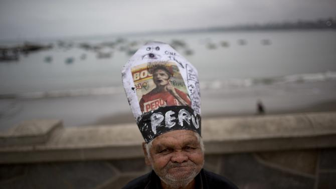In this June 29, 2015 photo, Carlos Humala poses for the picture wearing a makeshift hat resembling the Pope's, with a picture of soccer player Paolo Guerrero, during Saint Peter's day celebrations in Lima, Peru. During the feast day of the Catholic saint, who is the patron saint of fishermen, coastal communities pay homage to St. Peter, whose statue is paraded to the sea and petitions are made to keep their vessels and all who work on them safe. (AP Photo/Rodrigo Abd)