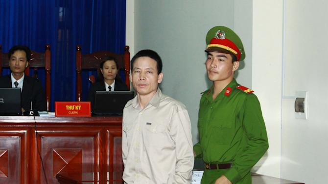 Doan Van Vuon is escorted to the courtroom in the northern city of Haiphong, Vietnam on Tuesday April 2, 2013. Vuon and three other relatives were charged with attempted murder when they attacked authorities who came to evict their fish farm injuring seven police and army officers in the incident last year. (AP Photo/Vietnam News Agency, Bui Doan Tan)
