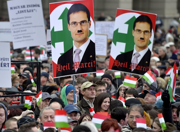 Participants hold a portrait of Hungarian lawmaker of Jobbik party Marton Gyongyosi showing him with a Hitler moustache as thousands of people attend a protest called Mass Demonstration Against Nazism in front of the Parliament building, unseen, in Budapest, Hungary, Sunday, Dec. 2, 2012. The protest has been provoked by MP Gyongyosi who demanded a list on Jewish Hungarians who are members of the Parliament or the government. (AP Photo/MTI, Laszlo Beliczay)