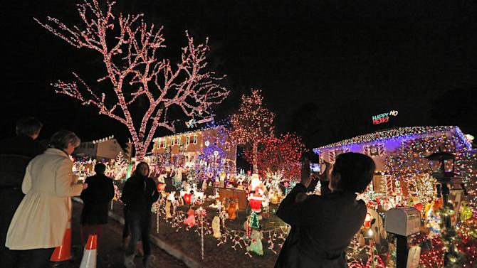 In this Tuesday, Dec. 11, 2012 photo, visitors take photos in front of homes decorated with thousands of holiday lights in Richmond, Va. (AP Photo/Steve Helber)