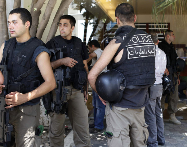 In this Aug. 9, 2012 photo, Lebanese security forces stand at the entrance building of former Lebanese Information Minister Michel Samaha as they raid his house after they arrested him. Samaha an ardent supporter of President Bashar Assad who has long acted as his unofficial media adviser, was arrested in a dramatic, high profile police operation on August 9, 2012 and subsequently indicted for plotting terror attacks in Lebanon at Syria's behest. The civil war in Syria is affecting its fragile, tiny neighbor Lebanon in countless ways and has already spilled over into sectarian street clashes, kidnappings and general government paralysis. (AP Photo)
