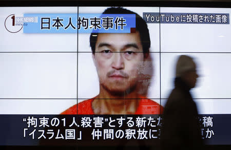 Man walks past screens displaying TV news programme showing image of Goto, one of two Japanese citizens taken captive by Islamic State militants, on a street in Tokyo