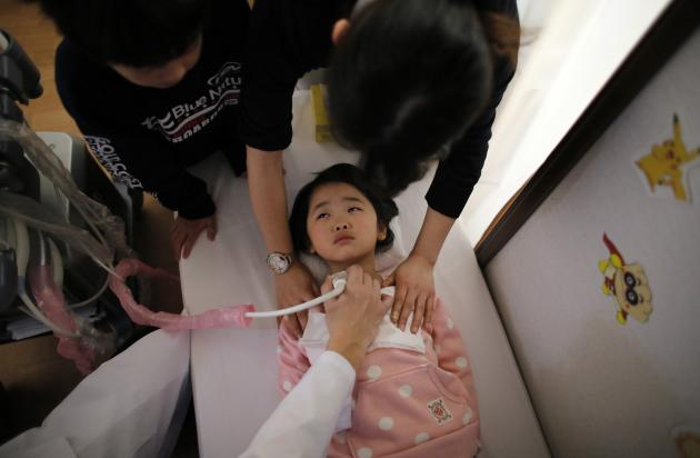 A doctor conducts a thyroid examination on five-year-old girl as her older brother and a nurse take care of her at a clinic in temporary housing complex in Nihonmatsu