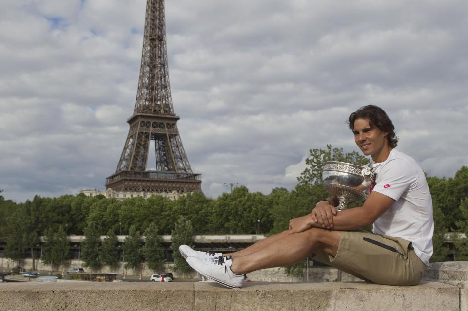 Rafael Nadal of Spain poses with the trophy after winning the men's final match against Novak Djokovic of Serbia at the French Open tennis tournament in Paris, Monday, June 11, 2012. Eiffel Tower seen in the background. (AP Photo/Michel Euler)