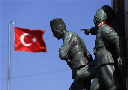 A Turkish flag flutters near the monument of Mustafa Kemal Ataturk at Taksim Square in Istanbul