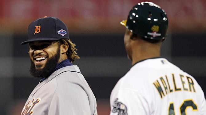 Detroit Tigers first baseman Prince Fielder, left, smiles at Oakland Athletics first base coach Tye Waller in the first inning of Game 4 of their American League division baseball series in Oakland, Calif., Wednesday, Oct. 10, 2012. (AP Photo/Ben Margot)