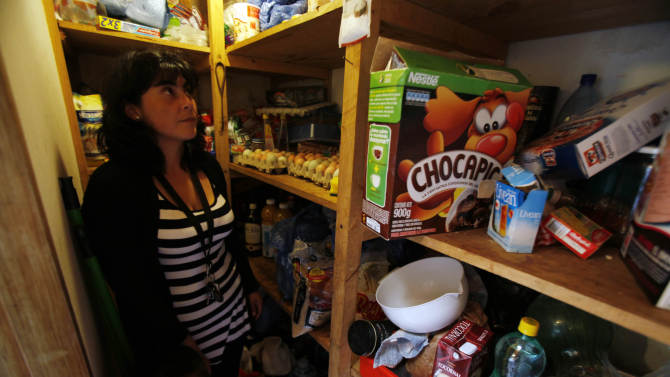 In this photo taken Nov. 29, 2012, Evelyn Perez and her son stand inside her pantry that she is mindful of keeping well stocked in anticipation of the next earthquake, in Navidad, Chile. Perez , 31, was seven months pregnant when she was jarred awake during the 2010 quake and stepped into the cold, dark streets dragging three kids to the safety of the hills.  After the dozens of recent tremors, she has also prepared a quake kit, which she keeps near her doorstep. (AP Photo/Luis Hidalgo)