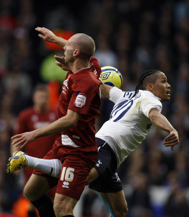 Tottenham's Steven Pienaar, right, vies for the ball with Cheltenham's Russell Penn during the FA Cup third round soccer match between Tottenham Hotspur and Cheltenham Town at White Hart Lane Stadium
