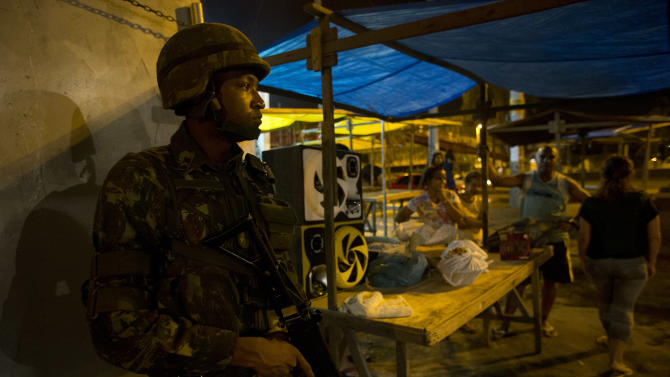 An Army soldier takes position while residents stand near him during an operation to occupy the Mare slum complex in Rio de Janeiro, Brazil, Saturday, April 5, 2014. More than 2,000 Brazilian Army soldiers moved into the Mare slum complex early Saturday in a bid to improve security and drive out the heavily armed drug gangs that have ruled the sprawling slum for decades. (AP Photo/Silvia Izquierdo)