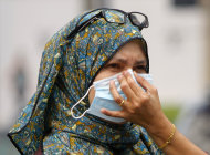 <p> A woman covers herself with a face mask as she walks on a street in downtown Kuala Lumpur, Malaysia, Monday, June 24, 2013. Malaysian authorities declared a state of emergency Sunday in a southern district where a smoky haze blamed on Indonesian forest fires has triggered one of the country's worst pollution levels in years. (AP Photo/Lai Seng Sin)
