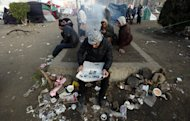 An Egyptian protester reads a local newspaper as he sits in Tahrir Square, in Cairo, Egypt, Thursday, Jan. 26, 2012. Egyptian protesters camp in Tahrir Square as they mark the first anniversary of the popular uprising that unseated President Hosni Mubarak. (AP Photo/Khalil Hamra)